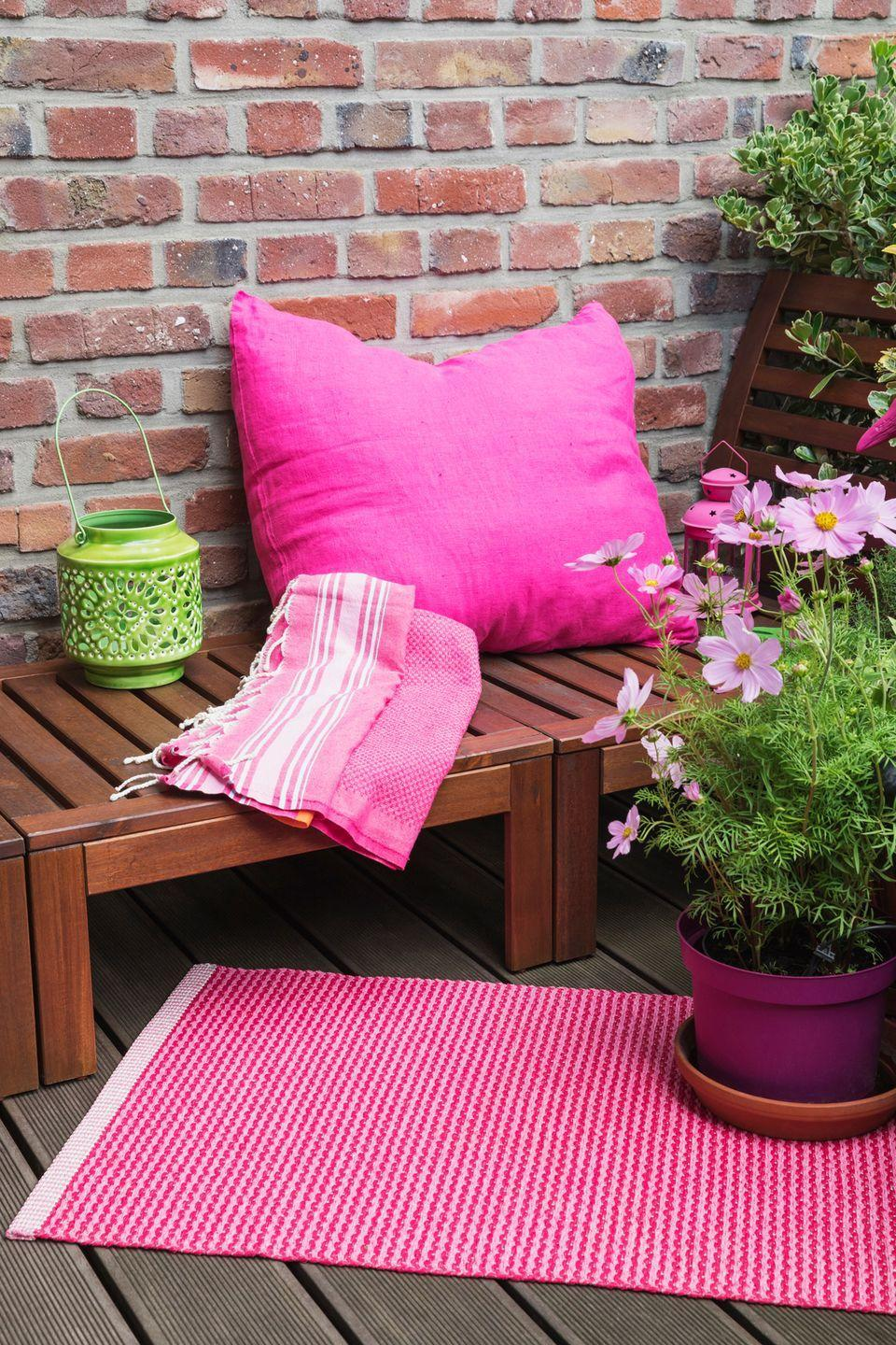 <p>Let your balcony's brick wall steal the show by enhancing it with an energetic pillow, throw and lantern. Don't forget the greenery!</p>
