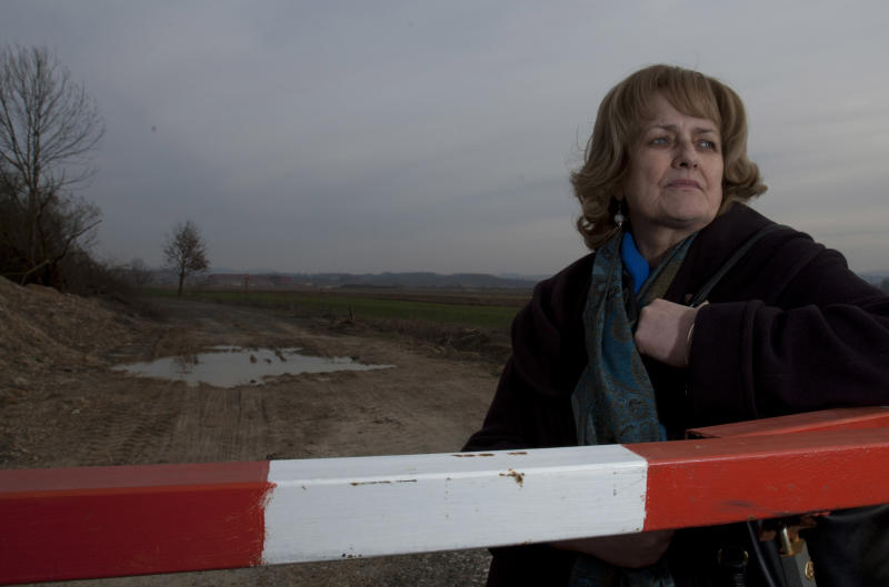 Muslim Bosniak woman Nusreta Sivac stands at the gate of Omarska, an iron ore mine outside her native town of Prijedor, 250 kms west of Sarajevo on Tuesday, March 5, 2013. During Bosnia's 1992-95 war the mine was used by Bosnian Serbs to detain and torture thousands of Muslim Bosniaks, including Sivac. Sivac was held there and systematically raped for over two months. After the war, Sivac begun collecting testimonies of other rape victims with a view to making a UN war crimes court in The Hague recognize it as a war crime. Today, largely because of Sivac, people are regularly prosecuted for wartime sexual violence. Omarska mine is today owned by the world's largest steel company Acellor Mittal and survivors of the war time atrocities there are not allowed access to the site. According to the UN, between 20,000 to 50,000 Bosnian women were raped , many in special rape camps , during the war that was fought between the new country's Serbs, Croats and Bosniaks. (AP Photo/Amel Emric)