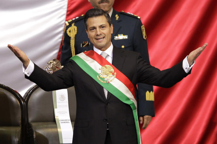 Mexico's incoming President Enrique Pena Nieto spreads out his arms after being sworn in at the inauguration ceremony in National Congress, in Mexico City, Saturday, Dec. 1, 2012. Pena Nieto took the oath of office as Mexico's new president on Saturday, bringing the old ruling party back to power after a 12-year hiatus amid protests inside and outside the congressional chamber where he swore to protect the constitution and laws of the land. (AP Photo/Alexandre Meneghini)