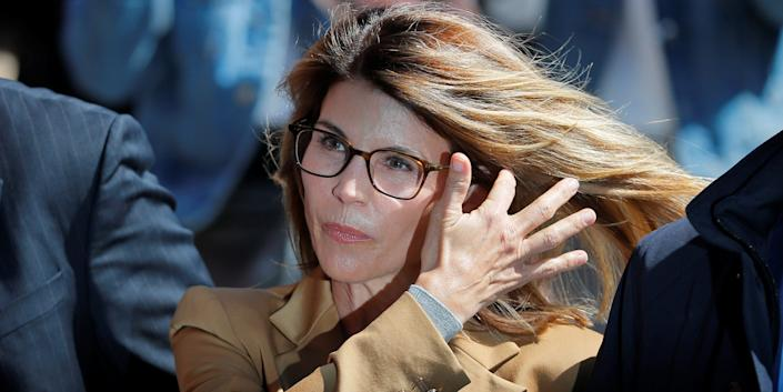 Actor Lori Loughlin, facing charges in a nationwide college admissions cheating scheme, is escorted to federal court in Boston, Massachusetts, in April 2019.