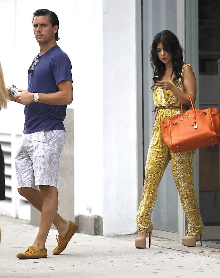 "Kourtney Kardashian and her boyfriend, Scott Disick, hit the shops of Manhattan on Monday. As always, the stars of ""Keeping Up With the Kardashians"" were all dressed up, with Scott in paisley shorts and suede moccasins, and Kourt in a bright, snakeskin-print jumpsuit and sky-high heels. <a href=""http://www.infdaily.com"" target=""new"">INFDaily.com</a> - July 11, 2011"