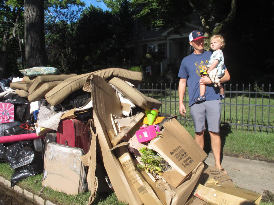 Dave Coughlin carries his 1-year-old son Thomas to their car to get him out of their flood-damaged home in Cranford N.J. on Saturday Sept. 4, 2021. His home, like many others impacted by the remnants of Tropical Storm Ida, has sewage in the basement that needs to be cleaned out. (AP Photo/Wayne Parry)