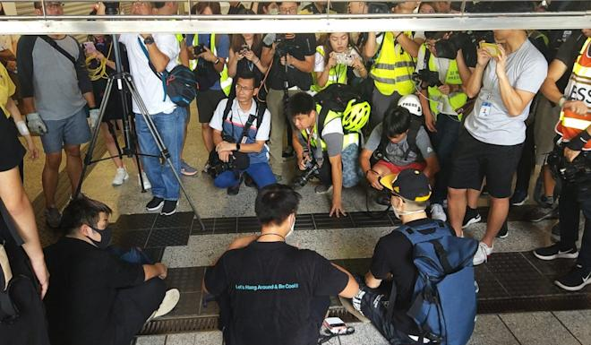 Protesters block the gate at Kwun Tong station from being closed. Photo: Linda Lew