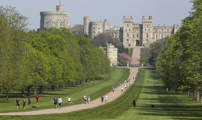 People exercise social distancing as they take their exorcise on the Long Walk in front of Windsor Castle during the Easter bank holiday weekend, as the UK continues in lockdown to help curb the spread of the coronavirus, in Windsor, England, Friday April 10, 2020.  The highly contagious COVID-19 coronavirus has impacted on nations around the globe, many imposing self isolation and exercising social distancing when people move from their homes. (Steve Parsons / PA via AP)