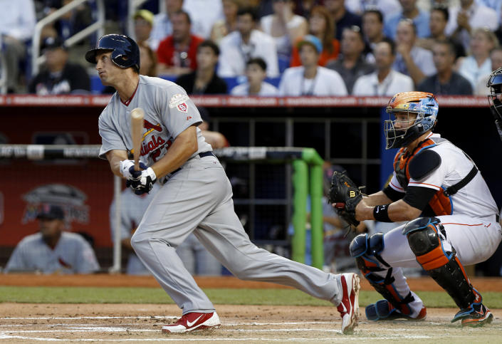 St. Louis Cardinals' David Freese follows through on a two-run single in the first inning during the Opening Day baseball game, Wednesday, April 4, 2012, in Miami. At right is Miami Marlins catcher John Buck. (AP Photo/Lynne Sladky)