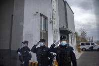 Police officers salute at the outer entrance of the Urumqi No. 3 Detention Center in Dabancheng in western China's Xinjiang Uyghur Autonomous Region on April 23, 2021. (AP Photo/Mark Schiefelbein)