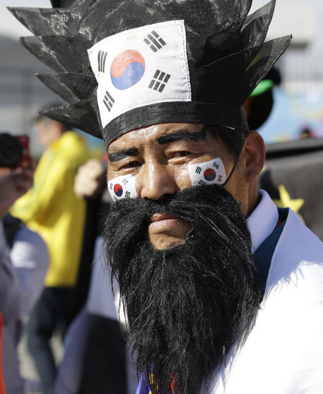 A South Korean fan wearing the traditional dress, arrives before the group H World Cup soccer match between South Korea and Belgium outside of the Itaquerao Stadium in Sao Paulo, Brazil, Thursday, June 26, 2014. (AP Photo/Lee Jin-man)