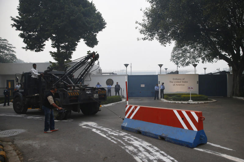 "Indian workers remove a barricade that had been erected as a safety measure outside the main entrance of U.S embassy, reportedly in retaliation to the alleged mistreatment of New York based Indian diplomat Devyani Khobragade, in New Delhi, India, Tuesday, Dec. 17, 2013. The arrest and strip search of an Indian diplomat in New York City escalated into a major diplomatic furor Tuesday as India's national security adviser called the woman's treatment ""despicable and barbaric."" (AP Photo/Saurabh Das)"