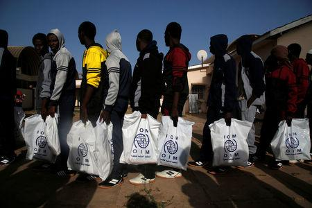 Gambian migrants deported from Libya stand in line as they wait for registration at the airport in Banjul