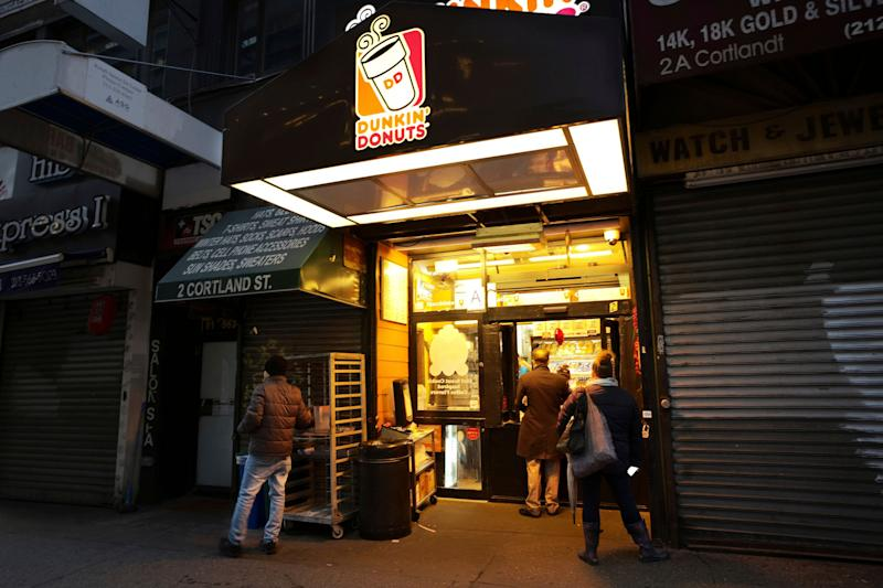 In this Wednesday, Feb. 6, 2019, photo customers arrive before dawn at a Dunkin' Donuts in New York. Dunkin' Brands Group Inc. reports financial results Thursday, Feb. 7. (AP Photo/Mark Lennihan)