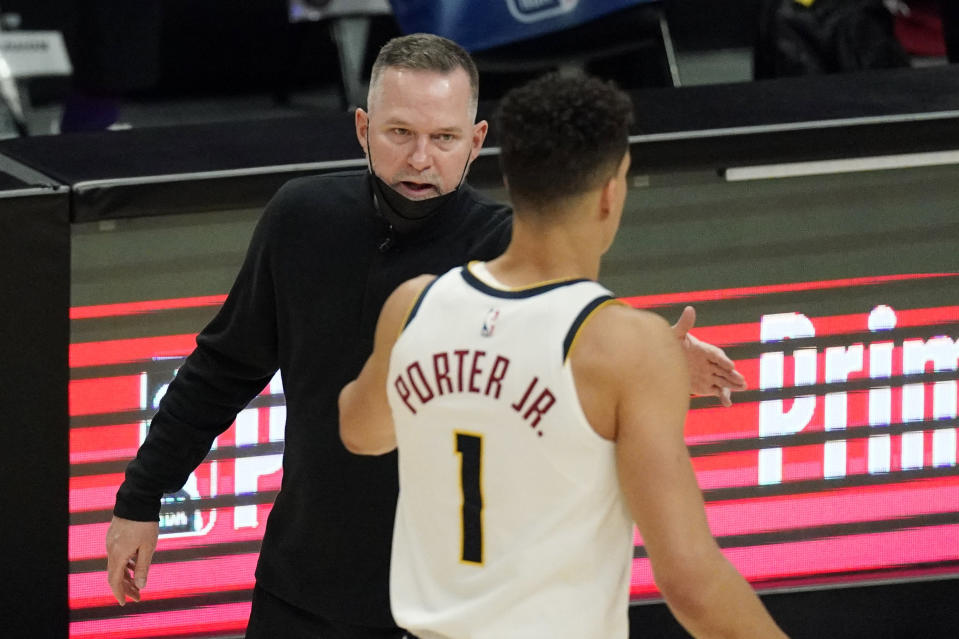 Denver Nuggets head coach Michael Malone, left, congratulates forward Michael Porter Jr. during a timeout in the second half of an NBA basketball game against the Los Angeles Clippers Saturday, May 1, 2021, in Los Angeles. (AP Photo/Mark J. Terrill)