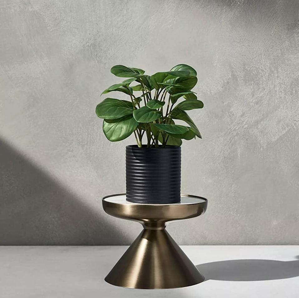 <p>This <span>Hilton Carter for Target Iron and Marble Plant Stand Gold</span> ($25) makes for a great gift.</p>