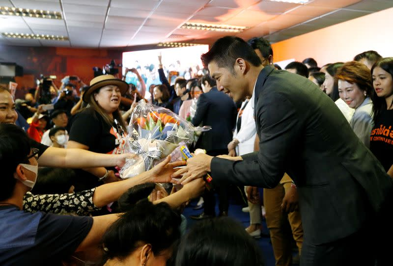 Supporters give flowers to Future Forward Party leader Thanathorn Juangroongruangkit as he arrives to give a speech, at the party's headquarters in Bangkok