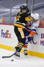 New York Islanders' Anders Lee (27) pushes the puck away as Pittsburgh Penguins' John Marino (6) checks him during the second period of an NHL hockey game, Saturday, Feb. 20, 2021, in Pittsburgh. (AP Photo/Keith Srakocic)