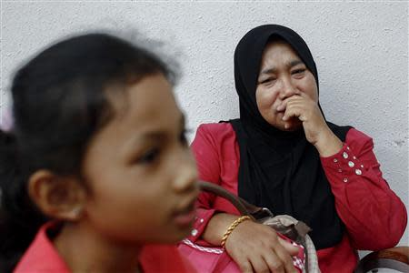 Rosila Abu Samah, 50, and her daughter Kaiyisah Selamat, 8, the mother and sister of flight engineer Mohd Khairul Amri Selamat who was on board missing Malaysia Airlines flight MH370, speak to journalists during an interview inside the hotel where they and other relatives of the passengers of the missing Boeing 777-200ER are staying in Putrajaya March 20, 2014. REUTERS/Samsul Said