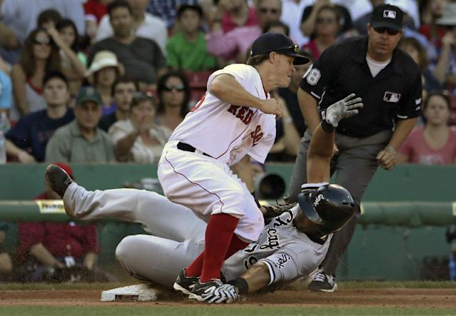 Boston Red Sox third baseman Brock Holt can't make the tag as Chicago White Sox' Jose Abreu, right, steals third base during the sixth inning of a baseball game at Fenway Park in Boston, Thursday, July 10, 2014. (AP Photo/Charles Krupa)