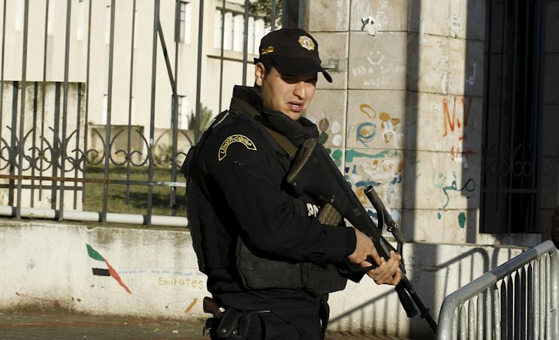 A Tunisian policeman stands guard near a presidential guard bus at the scene of a suicide bomb attack in Tunis