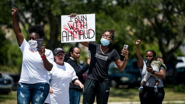 PHOTO: Demonstrators raise their fists at a parade of passing motorcyclists riding in honor of Ahmaud Arbery at Sidney Lanier Park on May 9, 2020 in Brunswick, Ga.  (Sean Rayford/Getty Images)