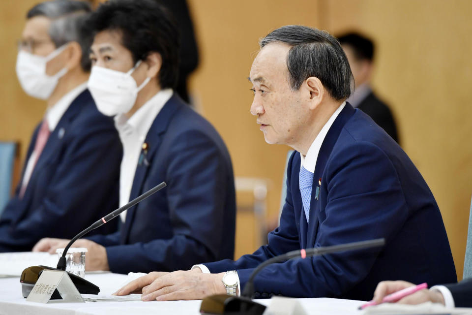 Japanese Prime Minister Yoshihide Suga, right, attends the government task force meeting for the COVID-19 measures at the prime minister's official residence in Tokyo Friday, May 28, 2021. Japan extended a coronavirus state of emergency in Tokyo and other areas for 20 more days on Friday, with infections not yet slowing to levels that would allow it to safely host the Olympics, which open in just over 50 days. (Yoshitaka Sugawara/Kyodo News via AP)