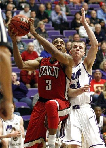 UNLV guard Anthony Marshall, left, goes to the basket past Portland guard David Carr during the first half of an NCAA college basketball game in Portland, Ore., Tuesday, Dec. 4, 2012. (AP Photo/Don Ryan)