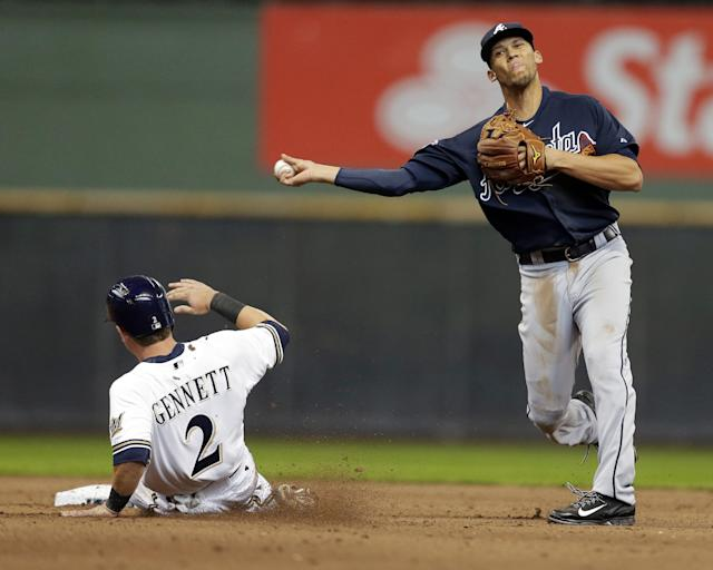 Atlanta Braves' Andrelton Simmons, right, forces out Milwaukee Brewers' Scooter Gennett and throws to first base for a double play on Brewers' Rickie Weeks in the seventh inning of an opening day baseball game Monday, March 31, 2014, in Milwaukee. (AP Photo/Jeffrey Phelps)