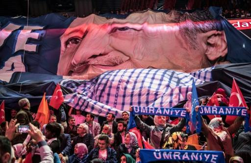 Supporters of Turkey's President Recep Tayyip Erdogan, unfurl his image as he gives his speech presenting his People's Alliance election strategy in Istanbul on May 6, 2018