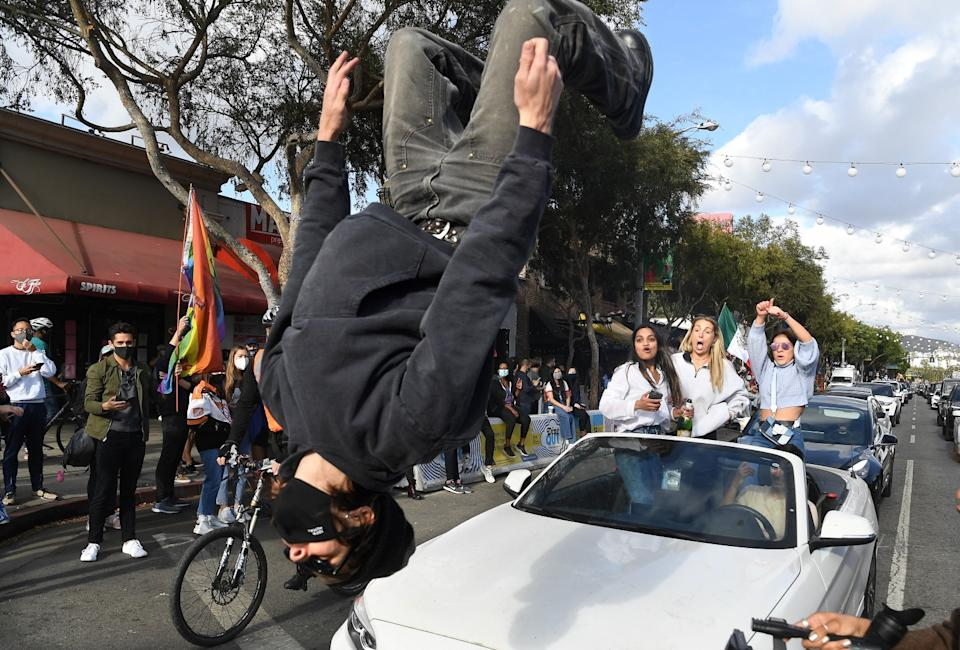A person does a back flip off the hood of a car in celebration along Santa Monica Boulevard in West Hollywood.