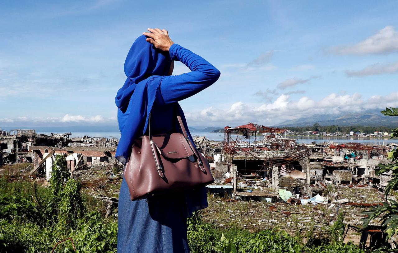 A woman looks at ruined houses, after residents were allowed to return to their homes for the first time since the battle between government troops and Islamic State militants began on May 2017, at the Islamic city of Marawi, Philippines April 19, 2018. REUTERS/Erik De Castro     TPX IMAGES OF THE DAY