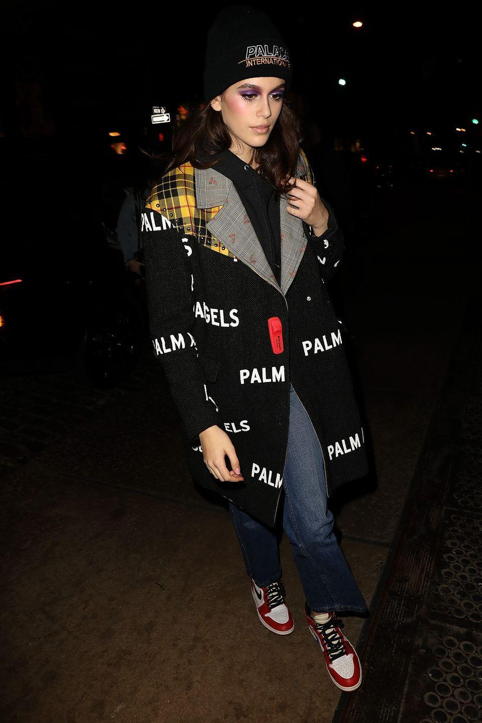 <p>Wrapping up for the cold, Gerber wore an oversized coat with the word 'palm' emblazoned on the front and a wooly hat</p>