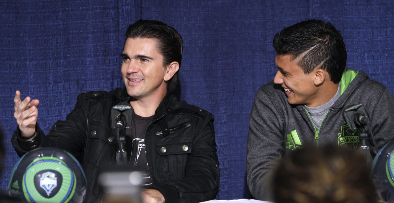 "Seattle Sounders FC forward Fredy Montero, right, smiles as he looks on during a news conference with Latin superstar musician Juanes about Juanes upcoming tour Tuesday, March 8, 2011, in Seattle. Juanes kicks-off his world ""P.A.R.C.E. Tour"" Thursday March 10, in Seattle."