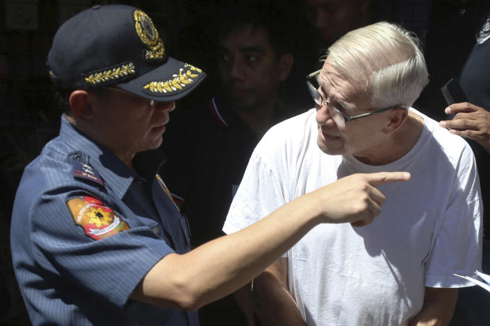 In this Feb. 19, 2019, photo, Philippine National Police, National Capital Region Police Chief Maj. Gen. Guillermo Eleazar, left, talks to Catholic priest Father Pius Hendricks prior to being served five more arrest warrants at the Regional Special Operations Unit at Camp Bagong Diwa in suburban Taguig, east of Manila, Philippines. Investigators say about 20 boys and men, one as young as 7, have accused the priest of sexual abuse at his parish in Talustosan village, Naval township, Biliran province in central Philippines. (AP Photo)