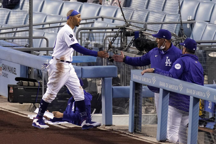 Los Angeles Dodgers' Mookie Betts, left, is congratulated by manager Dave Roberts after scoring on a single by Justin Turner during the first inning of a baseball game against the Colorado Rockies Wednesday, April 14, 2021, in Los Angeles. (AP Photo/Mark J. Terrill)