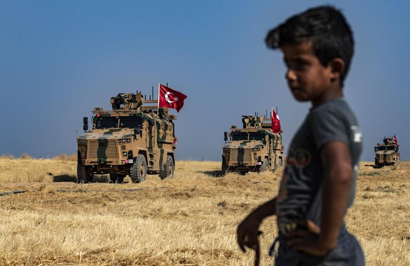 A Syrian boy watches as Turkish military vehicles, part of a US military convoy, take part in a joint patrol in the Syrian village on the outskirts of Tal Abyad town: AFP/Getty