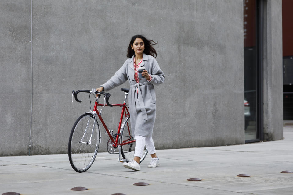 Woman walking to the office with a bike and coffee