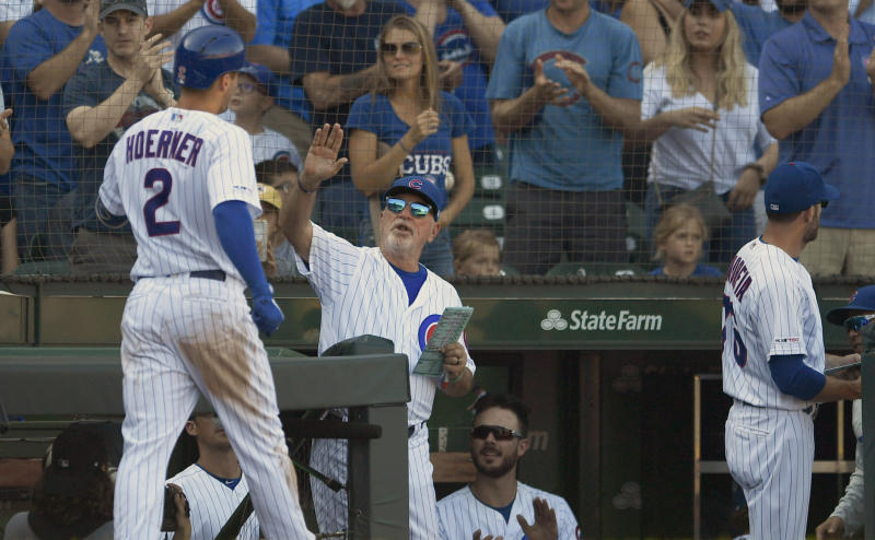 Chicago Cubs' Nico Hoerner (2) celebrates with manager Joe Maddon right, at the dugout after hitting a solo home run during the sixth inning of a baseball game against the Pittsburgh Pirates Saturday, Sept. 14, 2019, in Chicago. Chicago won 14-1. (AP Photo/Paul Beaty)