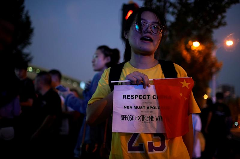 A woman holds a sign demanding NBA's apology outside the Mercedes-Benz Arena before the NBA exhibition game between Brooklyn Nets and Los Angeles Lakers in Shanghai. (Reuters)