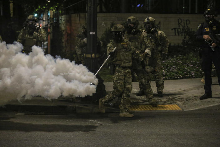 Police respond to protesters during a demonstration, Friday, July 17, 2020 in Portland, Ore. Militarized federal agents deployed by the president to Portland, fired tear gas against protesters again overnight as the city's mayor demanded that the agents be removed and as the state's attorney general vowed to seek a restraining order against them.(Dave Killen/The Oregonian via AP)