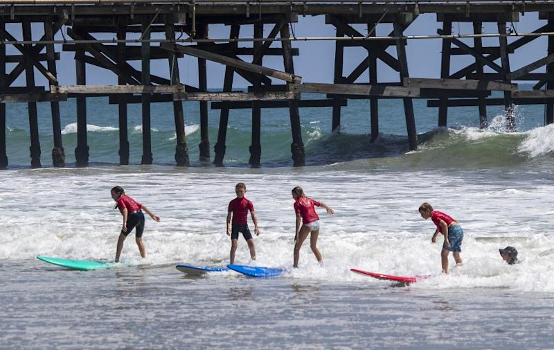 SAN CLEMENTE, CA - JUNE 30: Kids ride a wave together as they learn to surf on a warm Summer day at the San Clemente Pier Tuesday, June 30, 2020. Heal the Bay released its annual Beach Report Card and the San Clemente Pier made the top 10 list of beach bummers. (Allen J. Schaben / Los Angeles Times)