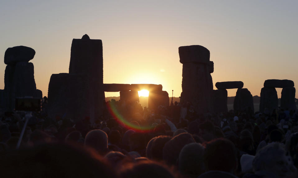 "FILE - In this June 21, 2019, file photo, the sun rises as thousands of revelers gather at the ancient stone circle Stonehenge to celebrate the Summer Solstice, the longest day of the year, near Salisbury, England. The coronavirus pandemic has scuttled summer solstice celebrations at Stonehenge, a highlight of the year for thousands of British pagans, druids and assorted revelers. English Heritage, which looks after the ancient stone circle, says restrictions on public events to slow the spread of the virus make it impossible to hold the event. It said it had decided to cancel the gathering ""after much deliberation and in consultation with our partners in the police and the emergency services, the druid and pagan community and others."" (AP Photo/Aijaz Rahi, File)"