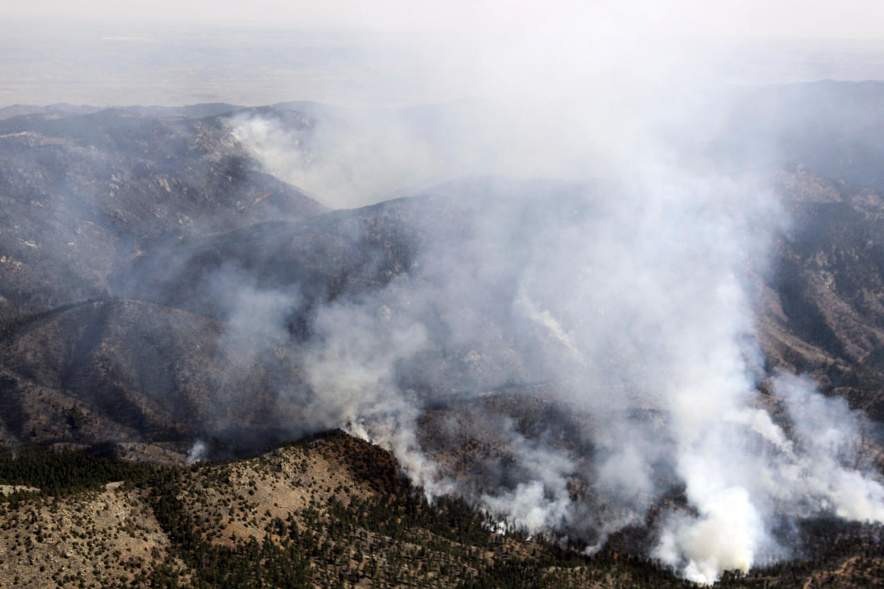 In this aerial photograph, smoke rises from the Lower North Fork Wildfire as it burns near the foothills community of Conifer, Colo., southwest of Denver on Tuesday, March 27, 2012. Firefighters are now able to actively battle the blaze on the ground that started on Monday and has already destroyed at least 16 homes in the rugged terrain. (AP Photo/David Zalubowski)