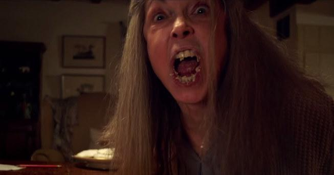 An elderly woman with a mouthful of food screams into the camera