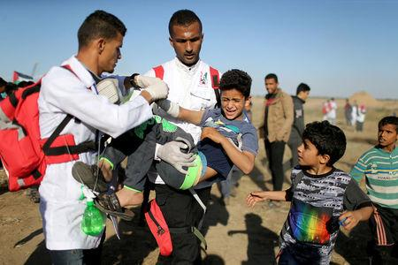 Wounded Palestinian boy is evacuated during a protest at the Israel-Gaza border fence in the southern Gaza Strip