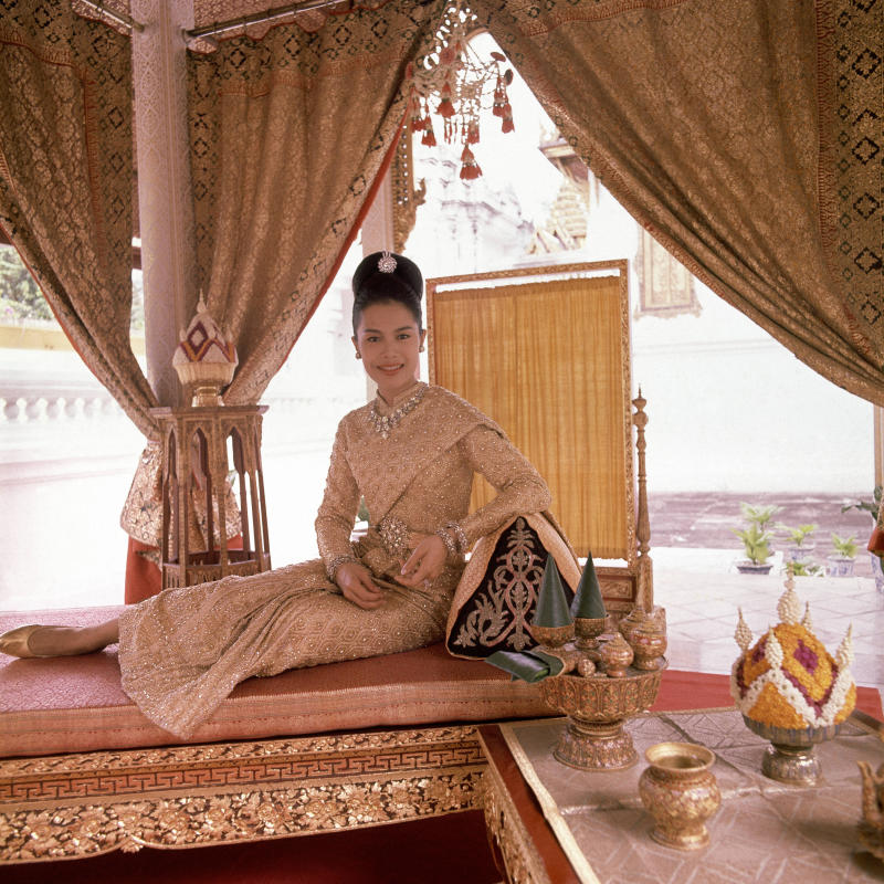 H.M. Queen Sirikit, seated on gold leafed bed in the King's coronation pavilion, wearing a dress of twenty-carat gold embossed crystal, with diamonds, which she wore to the Greek Royal wedding and was designed for her by Pierre Balmain, and diamond and gold jewelry. (Photo by Henry Clarke/Condé Nast via Getty Images)