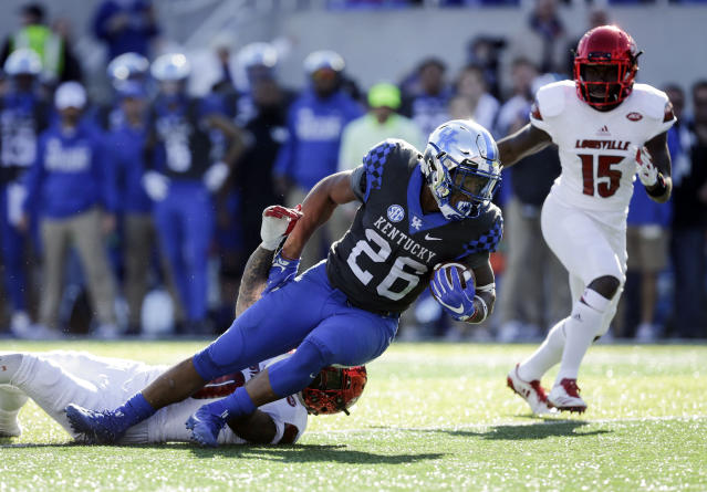 Kentucky running back Benny Snell Jr. is tackled by Louisville cornerback Jaire Alexander. (AP Photo)