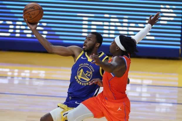 Andrew Wiggins, left, pictured driving to the basket against Oklahoma City Thunder's Luguentz Dort on May 8, will have to play a big role if Canada hopes to qualify for the Tokyo Olympics.  (Jed Jacobsohn/Associated Press - image credit)