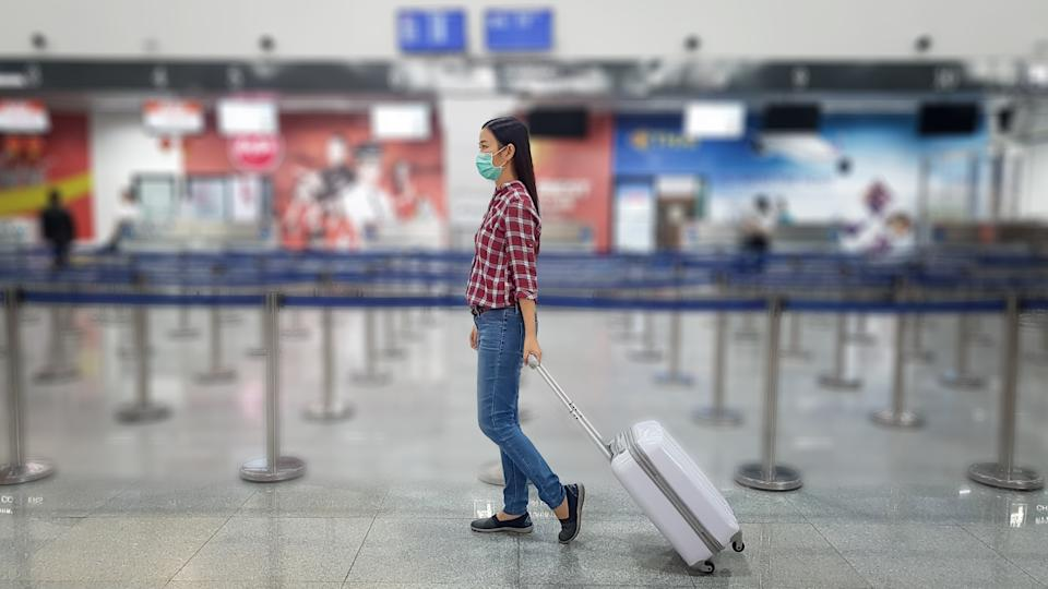 Asian tourist with luggage ,wearing mask to prevent coronavirus during travel time at the airport