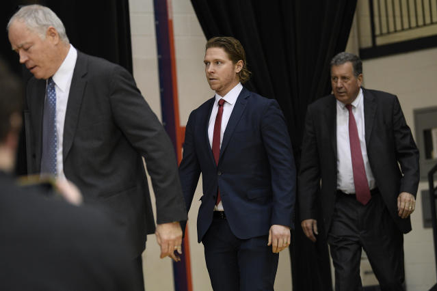 Washington Capitals center Nicklas Backstrom, center, of Sweden, arrives for an NHL hockey news conference about the Capitals re-signing him to a five-year contract, Tuesday, Jan. 14, 2020, in Washington. Also seen are Capitals president Dick Patrick, right, and general manager Brian MacLellan, at left. (AP Photo/Nick Wass)
