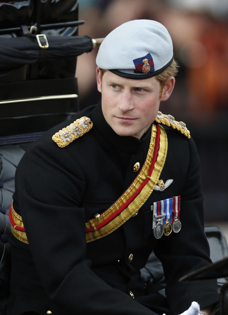 """File - In this Saturday, June. 15, 2013, file photo, Britain's Prince Harry arrives back to Buckingham Palace in a horse drawn carriage after the Trooping The Colour parade, at the Horse Guards Parade in London. Palace officials say that Prince Harry is ending his role as a helicopter pilot and taking up a new job with the army in London. Kensington Palace said Harry — known in the army as Capt. Wales — will now be organizing """"major commemorative events"""" involving the army. (AP Photo/Sang Tan, File)"""