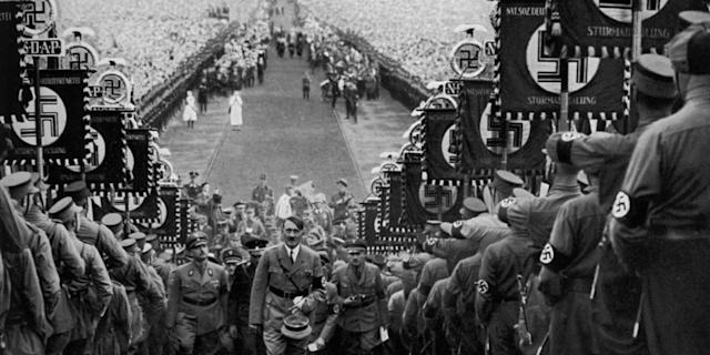 Adolf Hitler (1889-1945) climbing steps between ranks of Nazis holding swastika banners at the Bückeberg Harvest Festival. Huge crowds can be seen in the background. The Nazis staged a Reich harvest festival at the Bückeberg annually from 1933 until 1937. Photo: The Print Collector/Print Collector/Getty Images <br>
