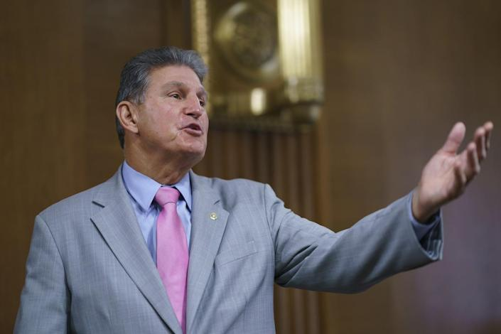 Joe Manchin reaches out with one hand as he speaks onstage.